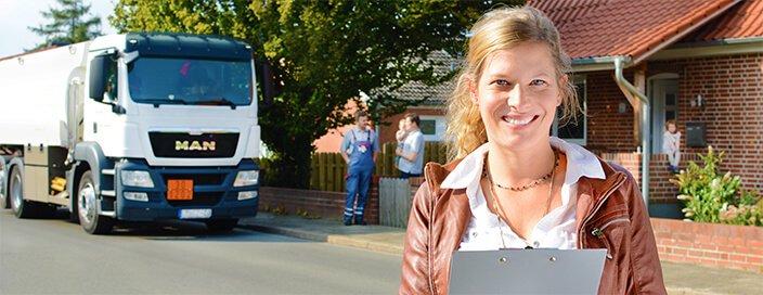 Im Vordergrund eine Frau mit Klemmbrett. Im Hintergrund Menschen vor einem Haus und ein Heizöl-Tankwagen